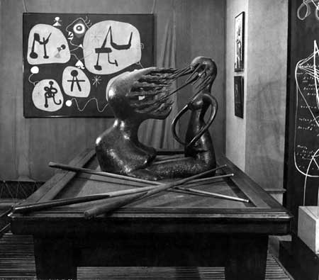 "Fig. 7. William Maywald, installation view of the Rain Room in the 1947 ""Exposition Internationale du Surréalisme,"" Galerie Maeght, Paris, with Maria Martins's sculpture Impossible on a billiard table and Joan Miró's Femme entendent la musique in the background. Vintage gelatin silver print on barite paper, Austrian Frederick and Lillian Kiesler Private Foundation, Vienna ©2013 Association Willy Maywald / Artist Rights Society (ARS), New York / ADAGP, Paris ©2013 Austrian Frederick and Lillian Kiesler Private Foundation, Vienna"